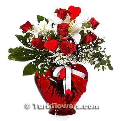 Kalp vazo içerisinde 7 adet kırmızı gül ve 1 dal kokulu lilyum