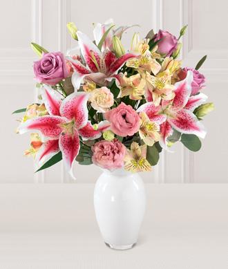 pembe lilyumlar ve pembe renkli mevsim çiçeklerinden oluşan aranjman