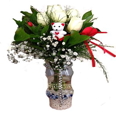 Cam vazo içerisinde 5 adet Beyaz gül ve Kalp çubuk dan oluşan aranjman