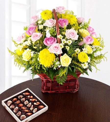 Sepet içerisinde güller  kasımpatılar ve çikolata dan  oluşan aranjman