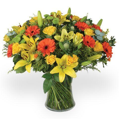 Cam vazo içerisinde sarı çiçeklerden oluşan aranjman